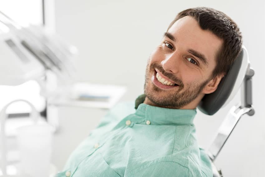 Man sitting in a dentists chair smiling at the camera