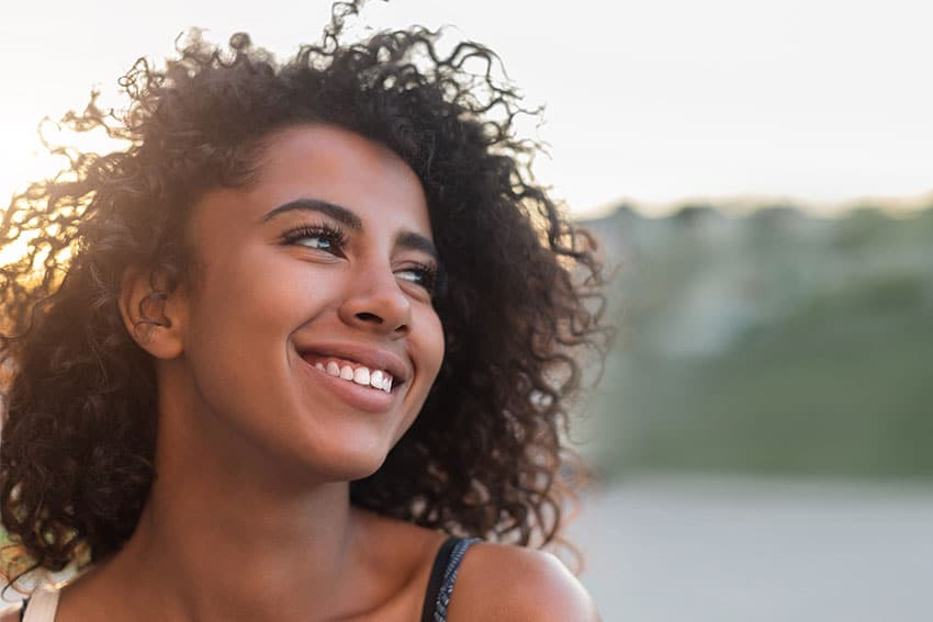 Younger woman smiling and looking off into the distance