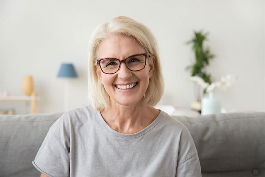 Older woman sitting on the couch smiling