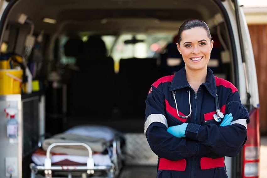Paramedic smiling outside her ambulance