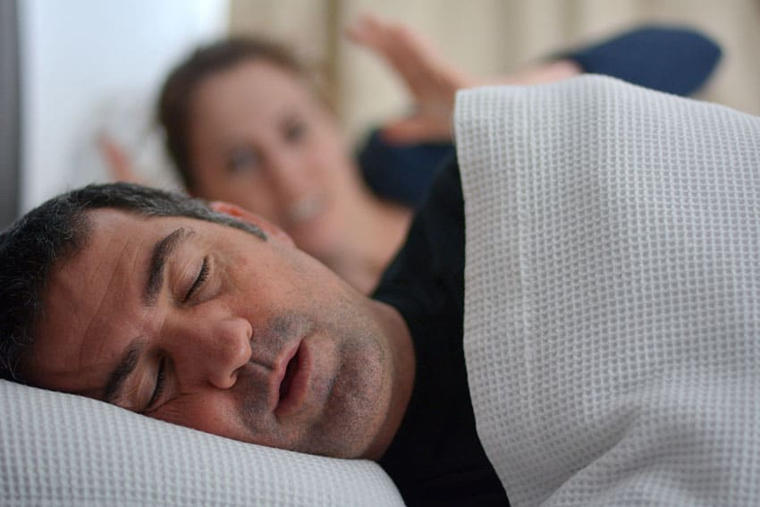 man snoring in bed while wife lays next to him, annoyed.